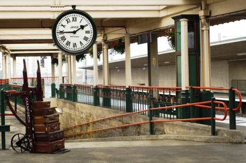 A porter's trolley loaded with suitcases at the top of a ramp below the station clock at Carnforth Station, a location used for the 1945 film 'Brief Encounter', Carnforth, Lancashire, England.
